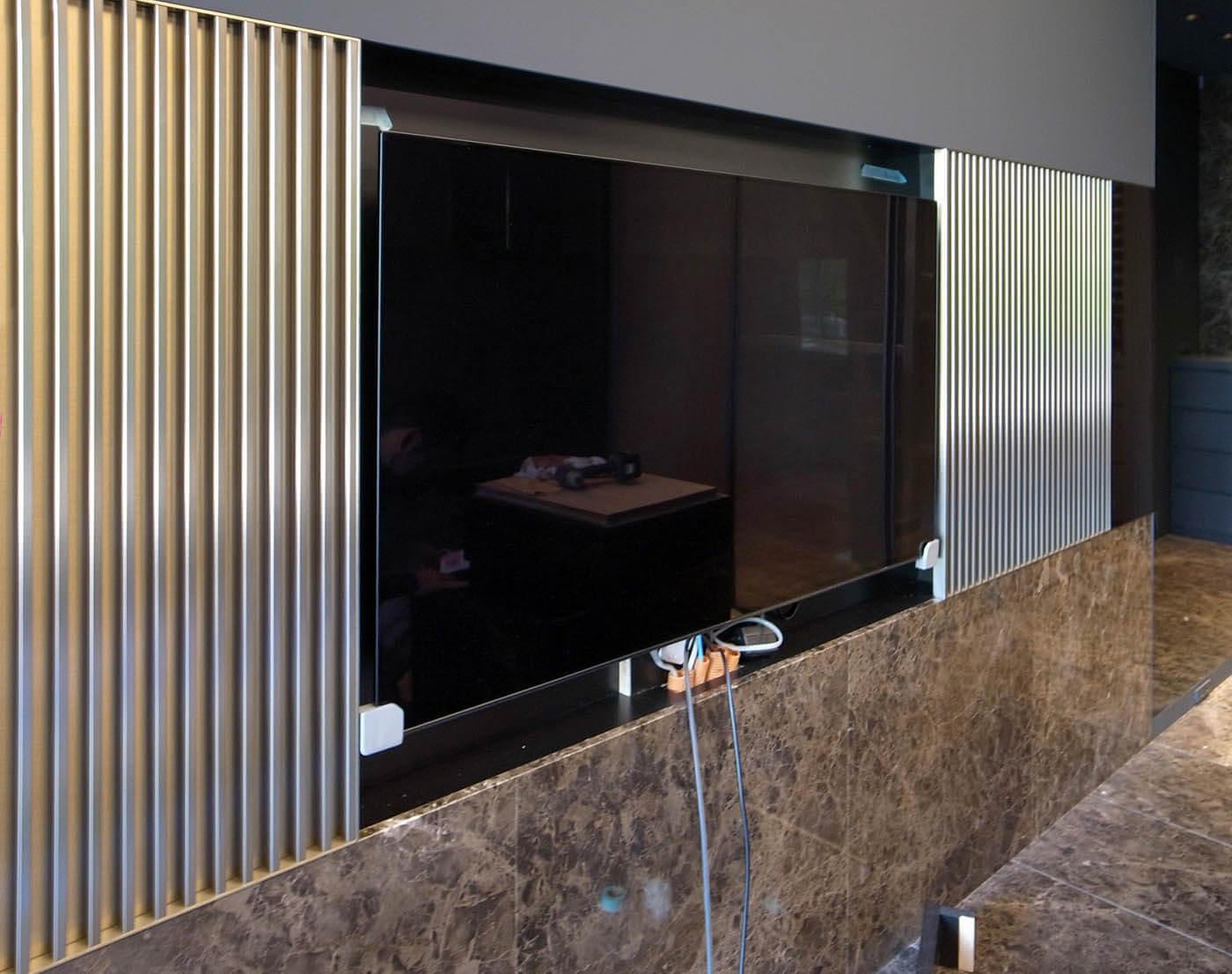 壁掛けテレビと両サイドの金属パネル
