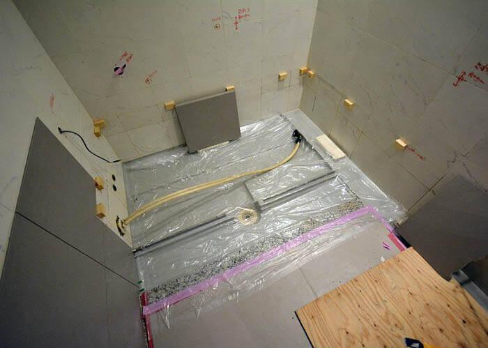 浴槽とエプロンパネルが撤去されたオーダーユニットバスの壁へのタイル張り